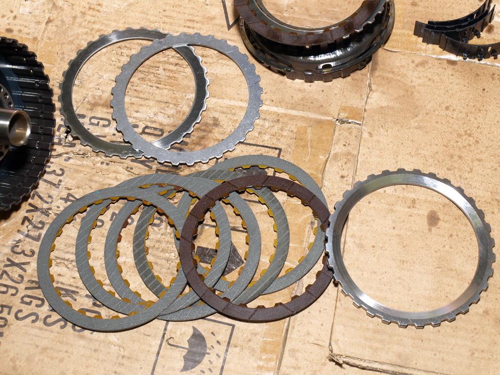 Новые и старый фрикционы, новое и старое стальное кольцо и новое запoрное кольцо.